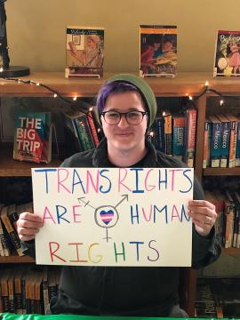 "Person holding a sign that reads ""Trans rights are human rights"""