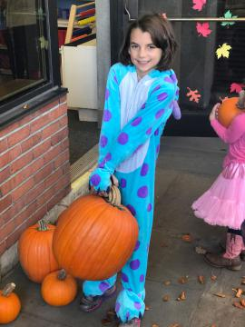 Girl in costume picks out her pumpkin