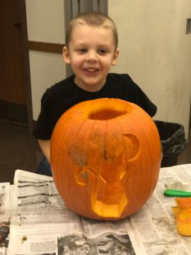 A child posing with his carved pumpkin