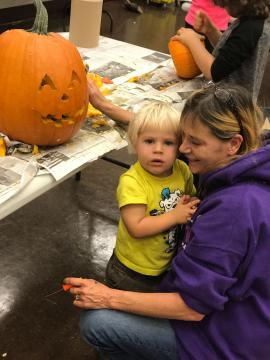 A child and woman carving a pumpkin together