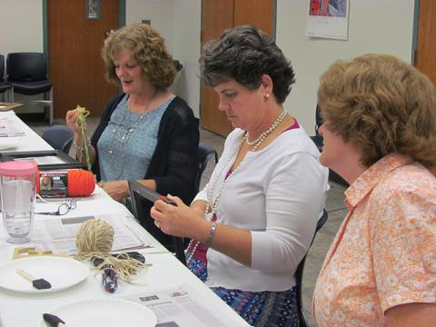 Craft program attendees begin adding yarn to their frames.