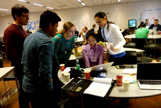 A team stands around a table while going over their ideas for Startup Weekend.